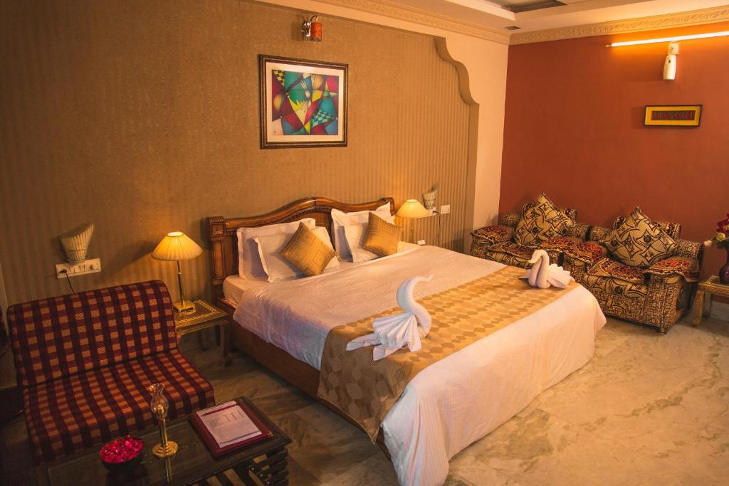 A bed or beds in a room at Hotel Meenakshi Udaipur