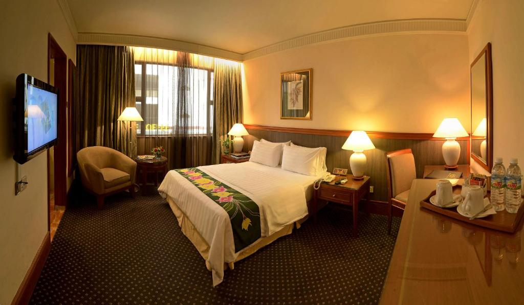 A bed or beds in a room at The Jesselton Hotel