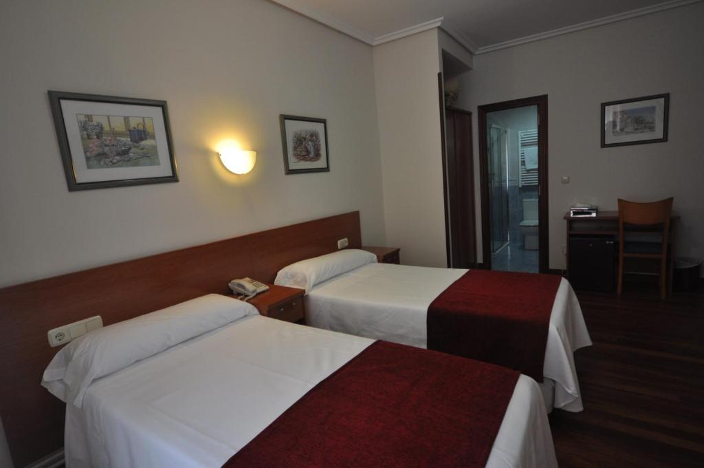 A bed or beds in a room at Pension Alameda