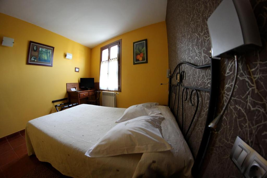 A bed or beds in a room at Hotel Rural Cuartamenteru