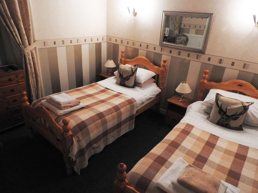 A bed or beds in a room at The Stag Head Hotel