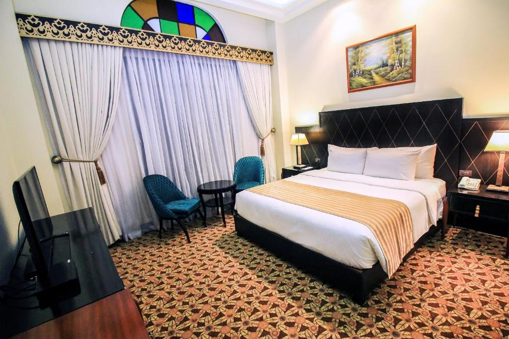A bed or beds in a room at The Luneta Hotel