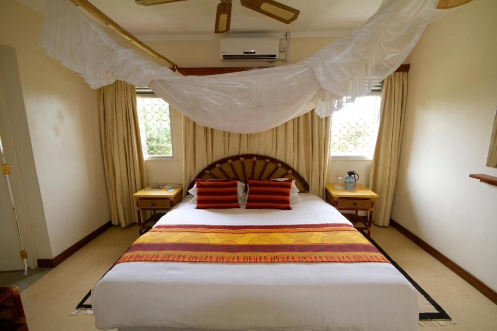 A bed or beds in a room at Mweya Safari Lodge