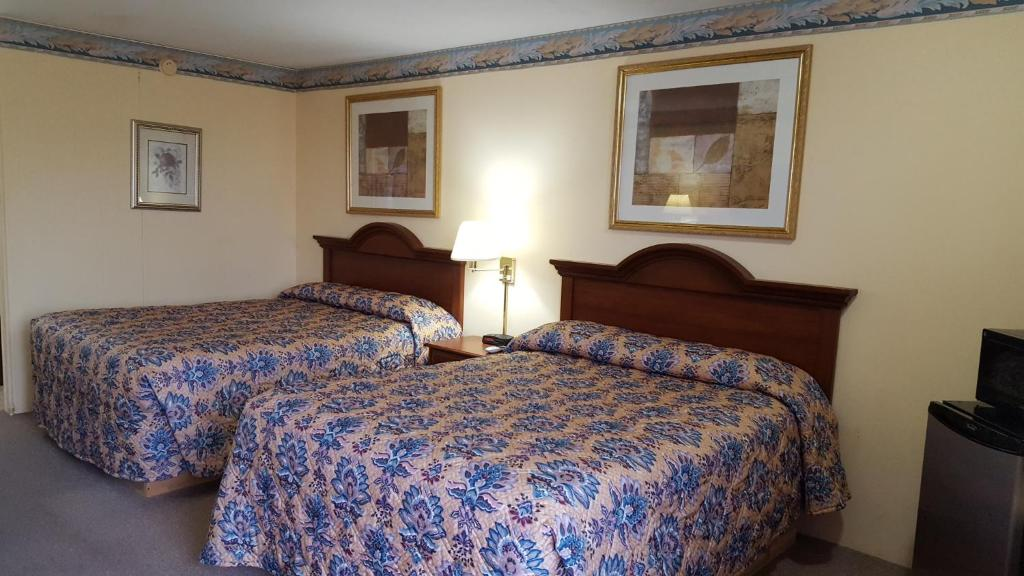 A bed or beds in a room at Innkeeper Motel Hamel