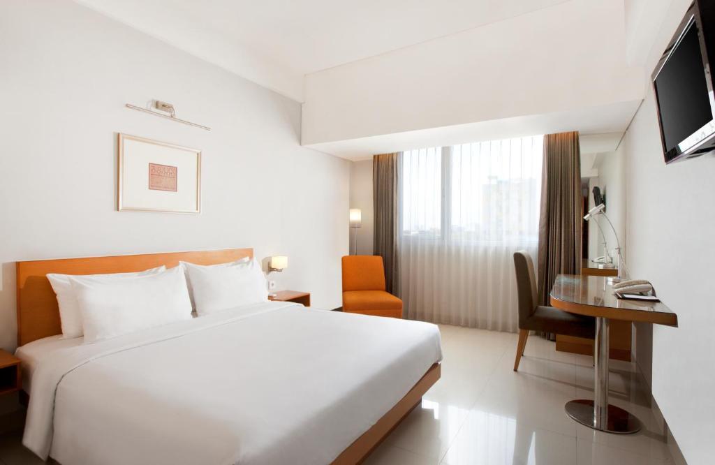 A bed or beds in a room at Hotel Santika Jemursari