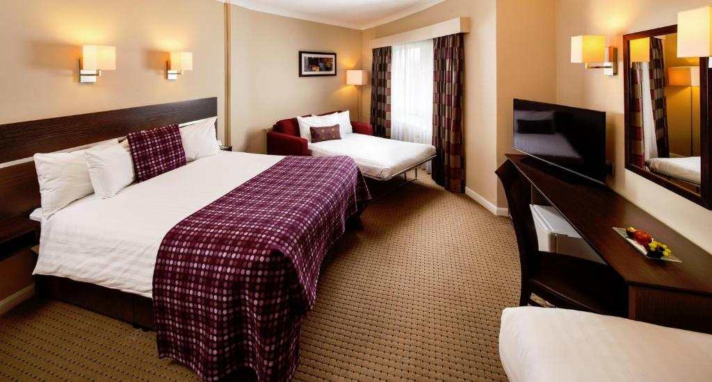 A bed or beds in a room at Mercure Chester Abbots Well Hotel