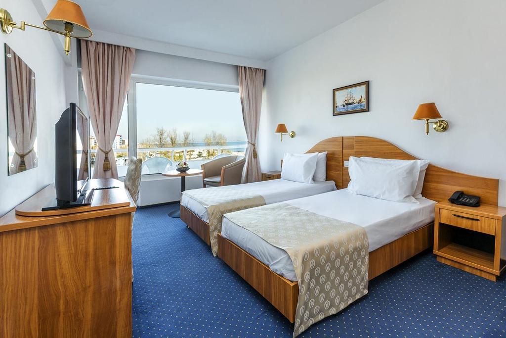 Un pat sau paturi într-o cameră la Savoy Hotel