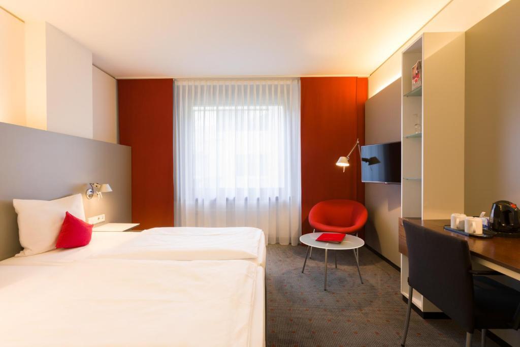 Een bed of bedden in een kamer bij Vienna House Easy MO. Stuttgart