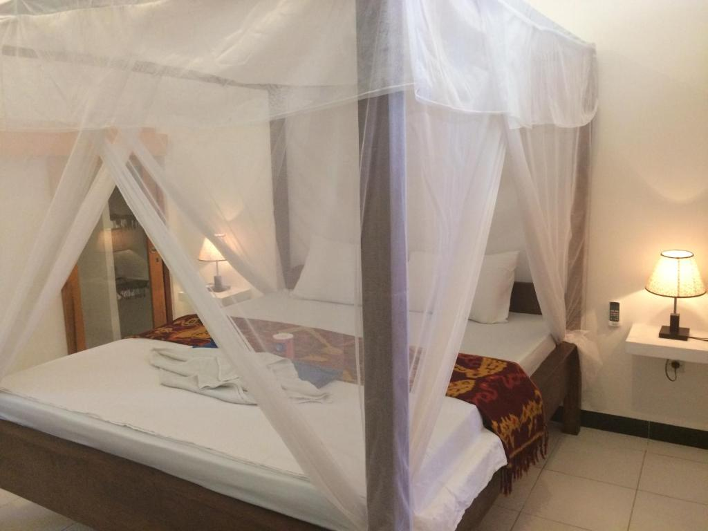 A bed or beds in a room at Gili Spoy - Spoy Homestay