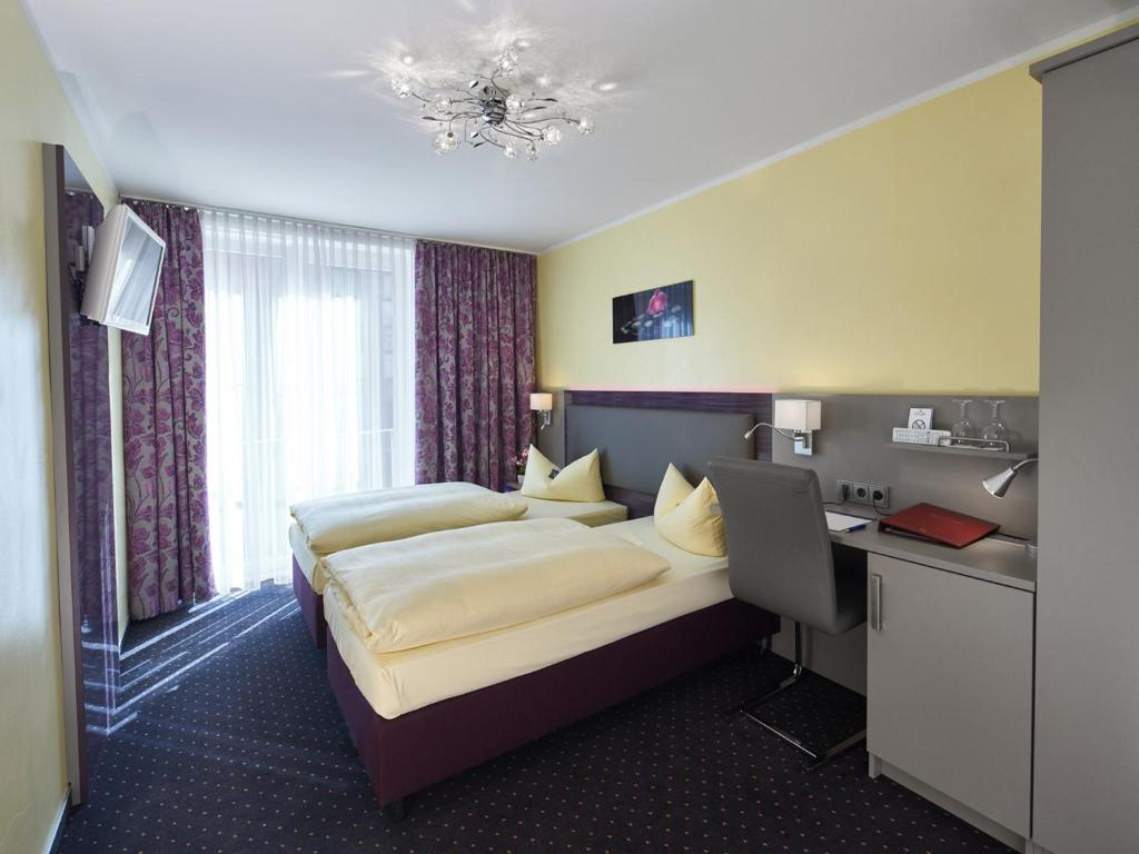 A bed or beds in a room at Hotel Alfa Zentrum