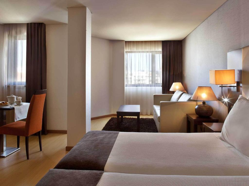 A bed or beds in a room at TURIM Iberia Hotel