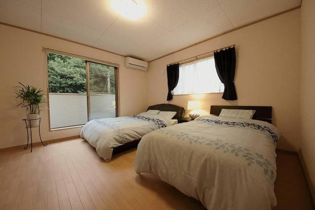 A bed or beds in a room at Yachimata Villa