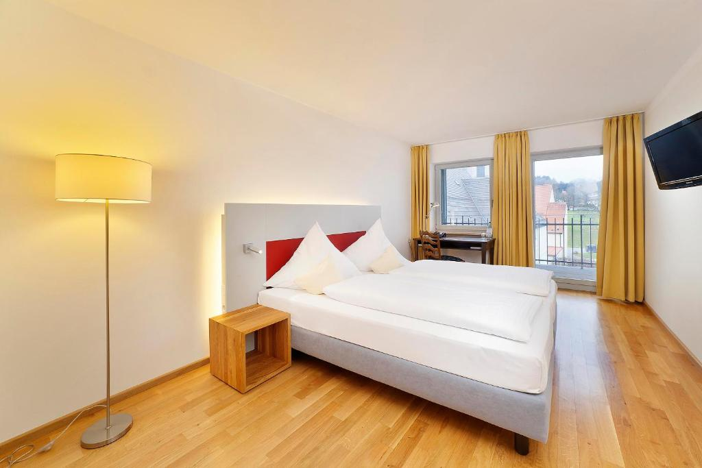 A bed or beds in a room at AKZENT Brauerei Hotel Hirsch