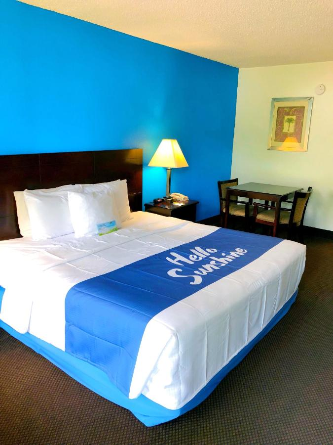 A bed or beds in a room at Days Inn by Wyndham Kissimmee FL