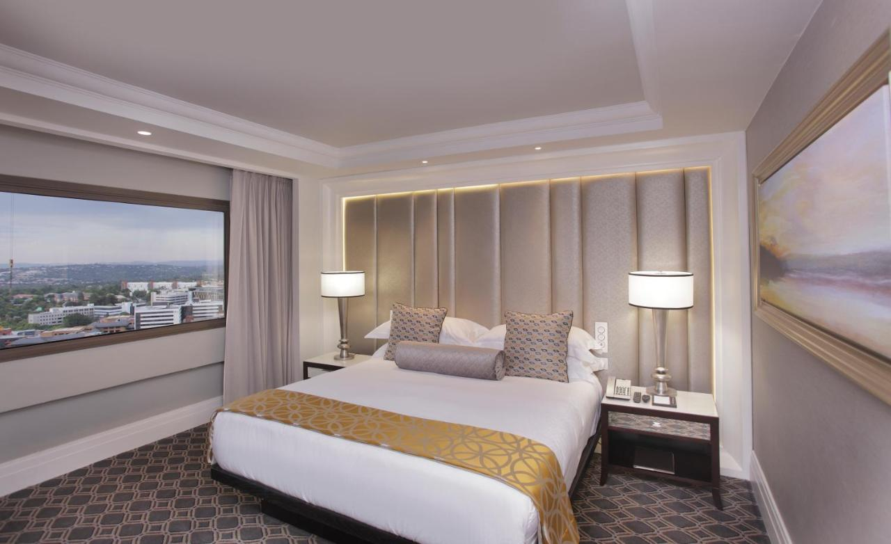 A bed or beds in a room at Sandton Sun