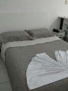 A bed or beds in a room at Flat Avenida Oceânica Barra