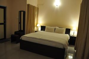 A bed or beds in a room at Jyothi Suites