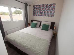 A bed or beds in a room at Holiday Home Green Resort Mooi Bemelen.1
