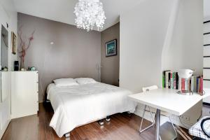 A bed or beds in a room at Welkeys Apartment - Rue Le Brun