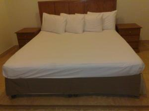 A bed or beds in a room at Assal Hail Hotel Apartments