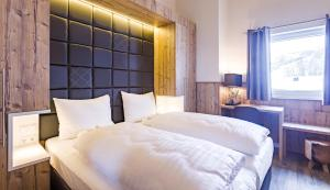 A bed or beds in a room at Avenida Mountain Lodges Saalbach by Alpin Rentals