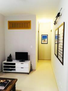 Una televisión o centro de entretenimiento en Apartamento Cabo Frio 3Q