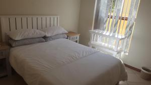 A bed or beds in a room at Sandbaai Hermanus