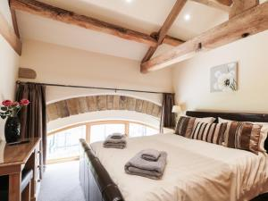 A bed or beds in a room at Stoneycroft Barn