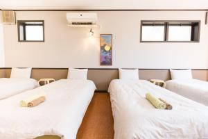 A bed or beds in a room at Guesthouse Meguri Inari