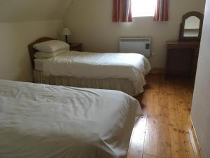 En eller flere senge i et værelse på Beach Cottage