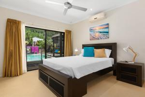 A bed or beds in a room at Private Large Cairns Family Home, Rainforest Views