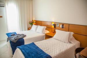 A bed or beds in a room at Atlantico Inn Apart Hotel