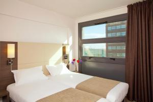 Un ou plusieurs lits dans un hébergement de l'établissement Séjours & Affaires Lille Europe