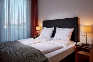 A bed or beds in a room at The Doorman Die Welle Frankfurt
