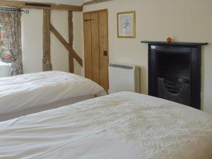 A bed or beds in a room at Thimble Cottage