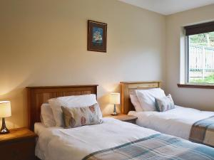 A bed or beds in a room at Barrmains Cottage