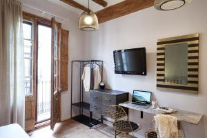 A television and/or entertainment center at AinB Gothic-Jaume I Apartments