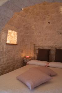 A bed or beds in a room at Trulli a Sud-Est