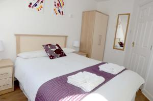 A bed or beds in a room at The Helm Apartments B&B