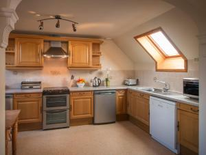 A kitchen or kitchenette at Carden Holiday Cottages