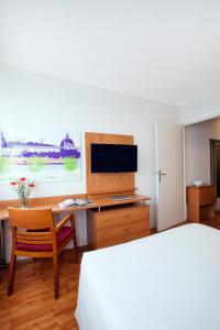 Una televisión o centro de entretenimiento en Séjours & Affaires Lyon Saint-Nicolas