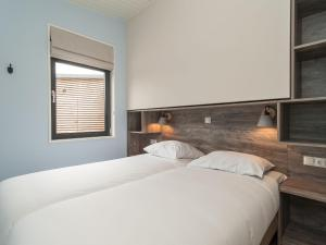 A bed or beds in a room at Sea Lodge Ameland 5