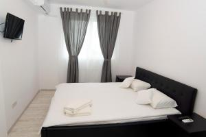 A bed or beds in a room at Denisa Apartamente