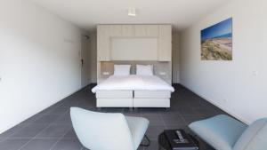 Een bed of bedden in een kamer bij Duinhotel Tien Torens