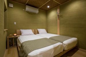 A bed or beds in a room at Kusamakura Kyoto Kawaramachi