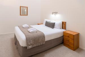 A bed or beds in a room at Courtenay Village