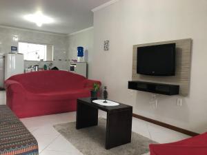 Una televisión o centro de entretenimiento en Apto 7 pessoas 500m do mar 015