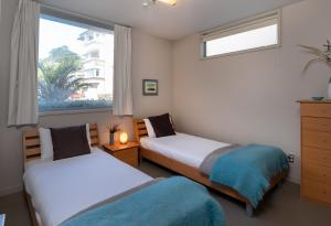 A bed or beds in a room at The Sands Waiheke