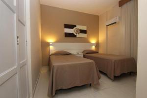 Un pat sau paturi într-o cameră la Gonzaga Flat (Technotel Ltda.)