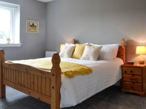 A bed or beds in a room at Black Bull Cottage